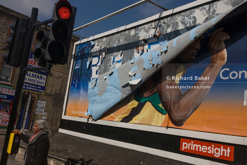 Peckham local and a Visa advertising billboard featuring the arm of Olympic athlete Usain Bolt in south London.