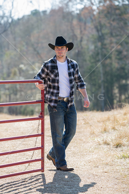 cowboy opening up a gate on a ranch