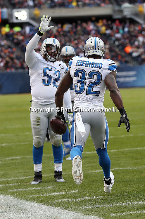 Detroit Lions strong safety James Ihedigbo (32) celebrates with Detroit Lions defensive end Darryl Tapp (52) after Ihedigbo intercepts a deflected end zone pass intended for Chicago Bears rookie wide receiver Cameron Meredith (81) during the NFL week 17 regular season football game against the Chicago Bears on Sunday, Jan. 3, 2016 in Chicago. The Lions won the game 24-20. (©Paul Anthony Spinelli)