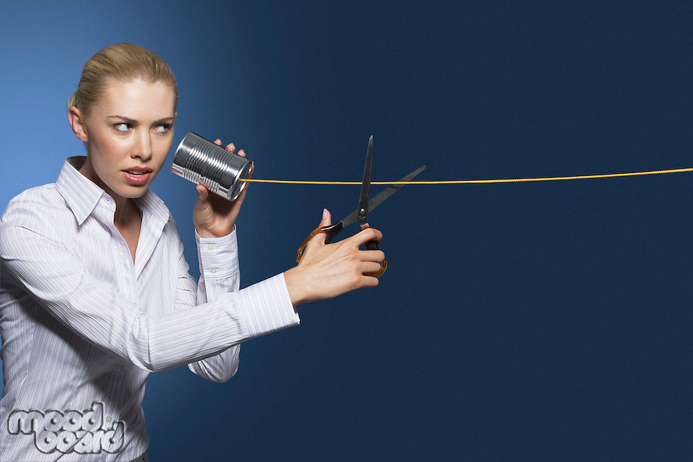 Woman cutting line on tin can string phone against dark background