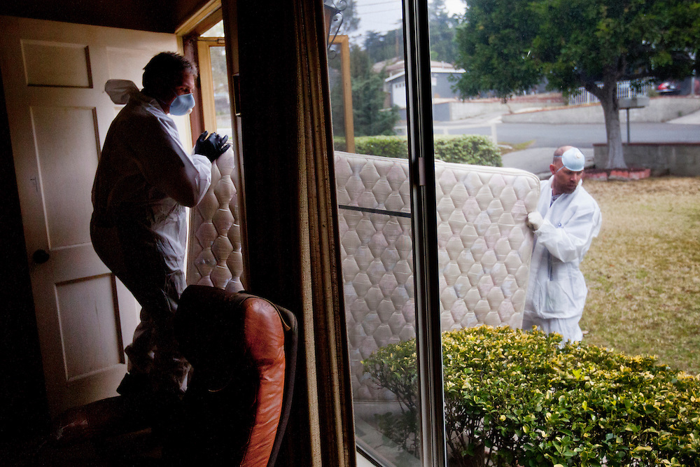 Ray Daniels and Timothy Tobola remove a mattress from a house upon which a man had passed away. Tuesday, March 13, 2012. Los Angeles, Calif. (photo by Gabriel Romero ©2012)