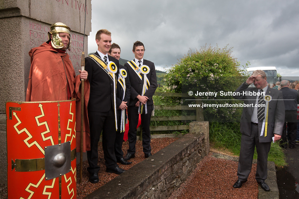 A stop during The Tour Of Ceremonies at the  commemorative stone which marks the location of Trimontium Roman Fort, which housed Emperor Agricola's troops in AD80, with Melrosian Sam Thomson being met by a Roman legionary, during the Melrose Festival, near Melrose, Scotland, Saturday 22nd June 2013. <br /> N55&deg;36.140'<br /> W2&deg;41.179'