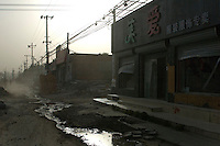 China, Beijing, Chaoyang, San Jian Fang, 2008. Months of demolition along Chaoyang Street have left businesses desperate to sell whatever they have - this store had its windows broken..