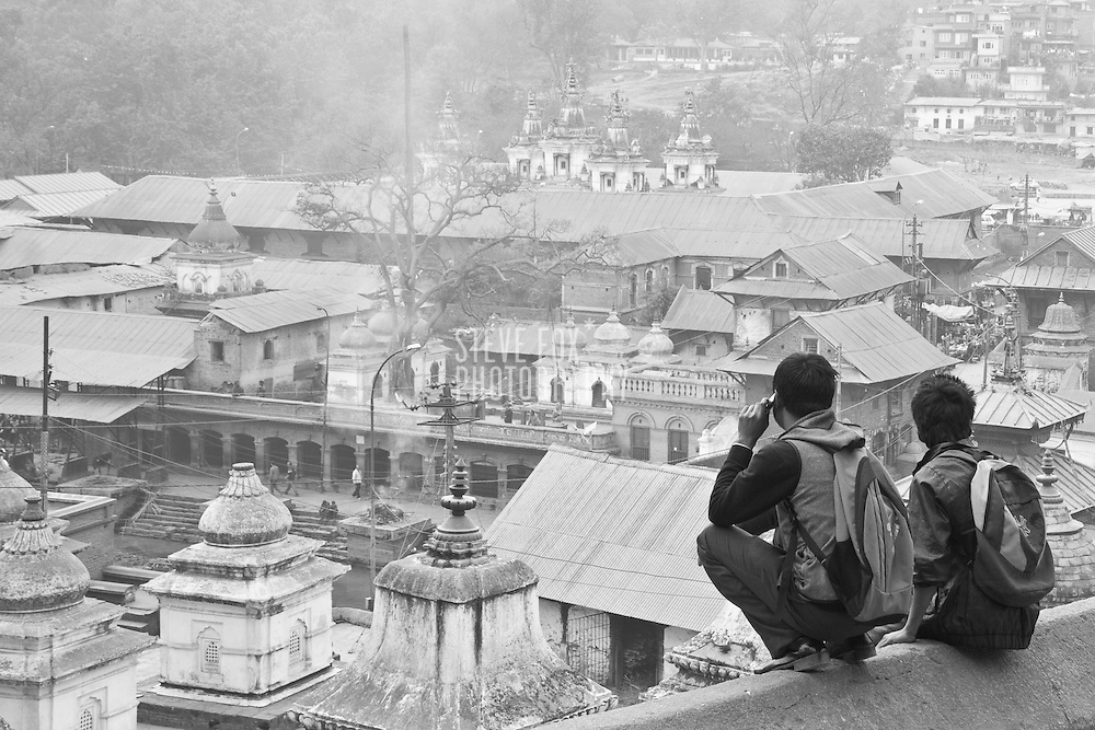 Two men gazing at the cremation Ghats of Bagmati river, Pashupati, Kathmandu, Nepal