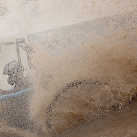 NAPLES, FL -- March 6, 2011 -- Water and mud flies envelopes a driver during the Swamp Buggy Races at the Florida Sports Park in Naples, Fla., on Sunday, March 6, 2011.  The races originated in the 1940's by bored hunters and draws thousands of fans three times a year to take in the buggies and jeep compete in the swamp. (Chip Litherland for ESPN the Magazine)