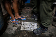 UK celebrity Myleene Klass (right) stands over one of the grave headstones as she speaks with Rose Marie Ferrer, 33, in Rose's house where she lives with her large family built over children's graves in an inhabited cemetery in Paranaque City, Metro Manila, The Philippines on 18 January 2013. Rose owns a shop in the cemetery where she sells funeral items. She supports her family with this, has breastfed all her 5 children, and is 9 months pregnant now. Photo by Suzanne Lee for Save the Children UK