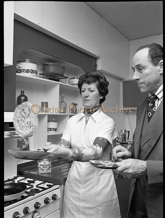 Pancake making At Ranks.   (K91)..1977..22.02.1977..02.22.1977..22nd February 1977..At Ranks experimental kitchen in Phibsborough, Dublin,Shiela Cunningham,Chief Adviser of Ranks Home Baking Service made the first pancakes of the day, today being Pancake Tuesday. While making the pancakes Ms Cunningham was surprised when an unexpected visitor dropped in. Mr Joseph Rank ,Chairman of the company ,called in to sample the first pancake of the day. He was in Dublin for the company's Annual General Meeting..While Shiela Cunningham tosses a pancake Mr Joseph Rank is pictured sampling one she prepared earlier.