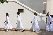 Young members of the praise dance group of the Mother Emanuel African Methodist Episcopal Church walk in line  following a ceremony marking the 2nd anniversary of the mass shooting June 17, 2017 in Charleston, South Carolina. Nine members of the historic African-American church were gunned down by a white supremacist during bible study on June 17, 2015.
