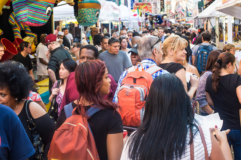 Weekend crowd at Feast of San Gennaro in Little Italy. Multiethnic mass of people slowly making their way past food booths, restaurants, and a variety of other booths. Jewelry, cigar making, sunglasses, Italian glass collectibles, much more. A kaleidoscope of delights. More than one million people attend every year. All the boroughs of New York and visitors from other countries compose the crowds. Major New York attraction since 1926. Top Ten rated must events and places to see in New York by Wikipedia.
