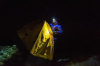 A female mountaineer in blue jacket erects a yellow tent on Glacier blanche on a cold winter night.