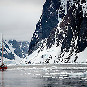 A sailboat carefully navigates the ice in the Lemaire Channel as it passes by steep rocky cliffs along the narrow channel.