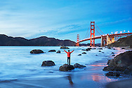 Scenic view of Golden Gate Bridge at sunset with a person standing on Marshall's Beach in the foreground. San Francisco, California, USA