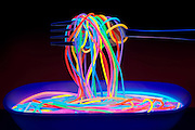 A fork wound in colorful glowing spaghetti above a bowl of pasta.Black light