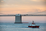 Een loodsboot vaart bij de Bay brug in San Francisco. De Amerikaanse stad San Francisco aan de westkust is een van de grootste steden in Amerika en kenmerkt zich door de steile heuvels in de stad.<br /> <br /> A pilot boat sails near the Baybridge in San Francisco. The US city of San Francisco on the west coast is one of the largest cities in America and is characterized by the steep hills in the city.