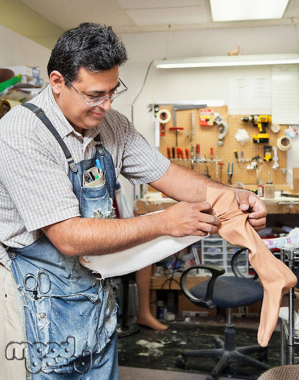 Mature male worker working on prosthetic limb