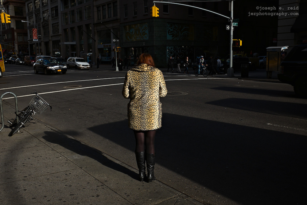Woman in animal print coat standing at curb, New York, NY, US