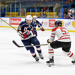 WHITBY, - Dec 18, 2015 -  Game #12 - Bronze Medal Game, Team Canada East vs. United States at the 2015 World Junior A Challenge at the Iroquois Park Recreation Complex, ON. Grant Jozefek #15 of Team United States tries to get the puck past Adam Smith #5 of Team Canada East during the first period.<br /> (Photo: Shawn Muir / OJHL Images)