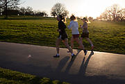 The day after UK Prime Minister Boris Johnson imposed unprecedented restrictions of movement for millions of Britons who were told to stay at home unless their key jobs or journeys were essential. Told to take a single exercise session per day, three women run in their local green space for a a sunset run n Brockwell Park in Herne Hill SE24, on 24th March 2020.