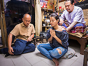 "25 MAY 2015 - BANGKOK, THAILAND:  PAT, a Thai woman getting a tattoo, gets a tattoo from AJARN NENG ONNUT in his Sak Yant tattoo parlor. Sak Yant (Thai for ""tattoos of mystical drawings"" sak=tattoo, yantra=mystical drawing) tattoos are popular throughout Thailand, Cambodia, Laos and Myanmar. The tattoos are believed to impart magical powers to the people who have them. People get the tattoos to address specific needs. For example, a business person would get a tattoo to make his business successful, and a soldier would get a tattoo to help him in battle. The tattoos are blessed by monks or people who have magical powers. Ajarn Neng, a revered tattoo master in Bangkok, uses stainless steel needles to tattoo, other tattoo masters use bamboo needles. The tattoos are growing in popularity with tourists, but Thai religious leaders try to discourage tattoo masters from giving tourists tattoos for ornamental reasons.       PHOTO BY JACK KURTZ"