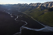 An aerial view of Alaska Highway cutting between the Trout River and the Sentinel Range of the Northern Rocky Mountains, in Muncho Lake Provincial Park, British Columbia.