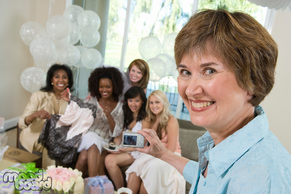 Woman photographing friends at bridal shower