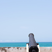 A lone rusty cannon aims towards the Atlantic Ocean at Cape Coast Castle, a UNESCO World Heritage Site located along the Gold Coast of Ghana.