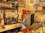 woman making expresso for customer in a bakery store