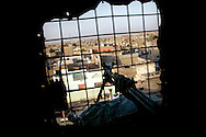 IRAQ, BASRA - JULY 4: A mounted rifle rests at the window of a lookout tower at a Military Training Team (MiTT) base in the poverty stricken neighbourhood of Hayaniyah, July 4, 2008 in Basra, Iraq. When British forces withdrew in 2007, Basra deteriorated into street battles between numerous Shiite militias and criminal gangs. In April 2008, Iraqi prime minister, Nouri al Maliki, sent two Iraqi army divisions to retake control of Basra. While the fighting has ended, unemployment is rife, at about 70 per cent. Since early 2008, Iraq's security situation has improved with oil production increasing, record government surplus and easing sectarian tensions.  (Photo by Warrick Page)