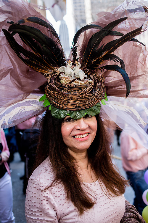 New York, NY - April 16, 2017. A woman with a hat topped by a bird's nest with chicks, and with a huge spray of feathers and gauze, at New York's annual Easter Bonnet Parade and Festival on Fifth Avenue.