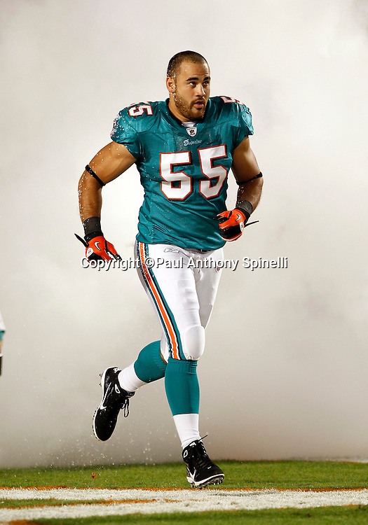 Miami Dolphins linebacker Koa Misi (55) enters the field in a cloud of smoke during pregame player introductions at the NFL week 11 football game against the Chicago Bears on Thursday, November 18, 2010 in Miami Gardens, Florida. The Bears won the game 16-0. (©Paul Anthony Spinelli)