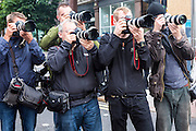 A group of five professional photographers standing in a London street with their camera kit and photographing an event as part of the IF campaign in London, United Kingdom.