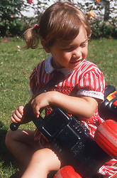 Young girl playing with toy bike outside in garden,