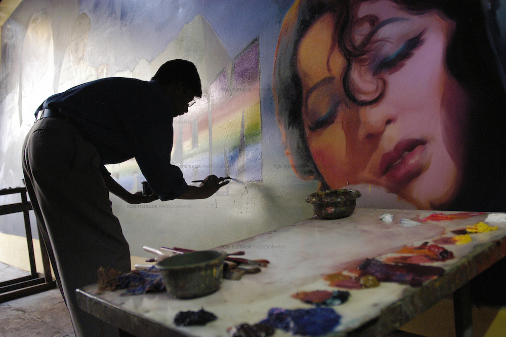 "A painter works on a canvas for the film ""Mughal-E-Azam"", staring Dilip Kumar and Madhubala, in the Ballakrinshna studio. ""Mughal-E-Azam"" was originally released in black and white in 1960. It has been re-released in 2004 having been ""coloured"" in post-production...Ballakrishna of Ballakrishna Art has been painting posters of Bollywood cinema stars for fifty years. Ballkrishna and his team of assistants produce paintings in a modest studio in central Bombay. With the advent of large, colour printing presses, Ballakrishna has been forced to diversify by painting posters for political rallies. He also paints canvasses for museums and private buyers in the West...Photo: Tom Pietrasik.Bombay, India .1.12.04...THIS PHOTOGRAPH IS THE COPYRIGHT OF TOM PIETRASIK. THE PHOTOGRAPH MAY NOT BE REPRODUCED IN ANY FORM OTHER THAN THAT FOR WHICH PERMISSION WAS GRANTED. THE PHOTOGRAPH MAY NOT BE STORED OR MANIPULATED WITHOUT PRIOR PERMISSION FROM TOM PIETRASIK...Tom Pietrasik.PHOTOGRAPHER.NEW DELHI.India tel: +91 9810614419.UK tel: +44 7710507916.Email: tom@tompietrasik.com.Website: tompietrasik.com"