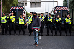 © London News Pictures. Calais, France. An immigrant stands in front of a line of French police preventing access to the Eurotunnel complex. Migrants attempting to reach the UK via the Eurotunnel at Calais in France. The situation has reached crisis point, which French police over run by attempts to cross the border. Photo credit: Ben Cawthra /LNP