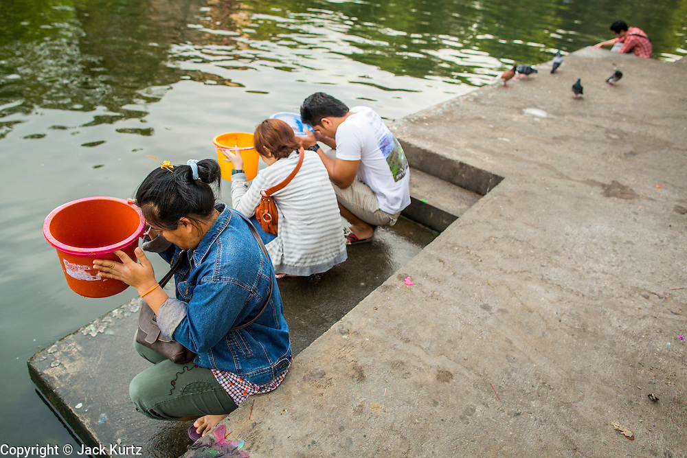 04 JANUARY 2012 - BANGKOK, THAILAND:  People pray before releasing fish and snails into Khlong Phra Khanong at Wat Mahabut in eastern Bangkok. The temple was built in 1762 and predates the founding of the city of Bangkok. Just a few minutes from downtown Bangkok, the neighborhoods around Wat Mahabut are interlaced with canals and still resemble the Bangkok of 60 years ago. Wat Mahabut is a large temple off Sukhumvit Soi 77. The temple is the site of many shrines to Thai ghosts. Many fortune tellers also work on the temple's grounds.   PHOTO BY JACK KURTZ