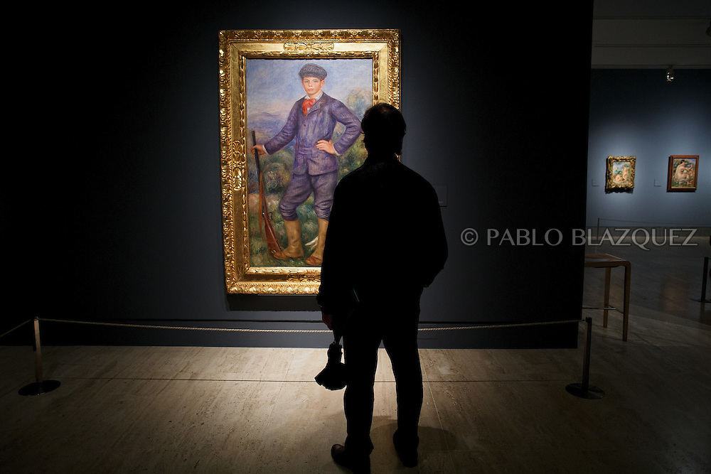 A member of the press looks at Pierre Auguste-Renoir's work 'Jean as a Huntsman', painted in 1910 at the Museum Thyssen-Bornemisza on October 17, 2016 in Madrid, Spain. 'Renoir: Intimacy' features 78 works by French painter Renoir (1841-1919) borrowed from museums and collections from around the world and will be open to the public from October 18, 2016 to January 22, 2017 (© Pablo Blazquez)