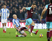 Marko Arnautović of West Ham United is tackled by Huddersfield Town's Aaron Mooy  during the Premier League match between Huddersfield Town and West Ham United at the John Smiths Stadium, Huddersfield, England on 13 January 2018. Photo by Paul Thompson.
