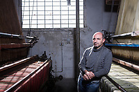"""SOVERIA MANNELLI, ITALY - 17 NOVEMBER 2016: Emilio Salvatore Leo (41), entrepreneur and heir of the woolen mill and historic family business Lanificio Leo, poses for a portrait by a Jacquard loom (a power loom that simplifies  the process of making textiles) in Soveria Mannelli, Italy, on November 17th 2016.<br /> <br /> Lanificio Leo was the first and last machine-operated woolen mill of Calabria, founded in 1873, it employed 50 people until the 1970s, when national policies to develop Italy's South cut out small businesses and encouraged larger productions or employment in the public administration.<br /> <br /> The woolen mill was on stand-by for about two decades, until Emilio Salvatore Leo, 41, started inviting international designers and artists to summer residencies in Soveria Mannelli. With their inspiration, he tried to envision a future for his mill and his town that was not of a museum of the past,<br /> Over the years, Mr. Leo transformed his family's industrial converter of Calabrian wool into a brand that makes design products for home and wear. His century old machines now weave wool from Australia or New Zealand, cashmere from Nepal and cotton from Egypt or South America. He calls it a """"start-up on scrap metals,"""" referring to the dozens of different looms that his family acquired over the years.<br /> <br /> Soveria Mannelli is a mountain-top village in the southern region of Calabria that counts 3,070 inhabitants. The town was a strategic outpost until the 1970s, when the main artery road from Naples area to Italy's south-western tip, Reggio Calabria went through the town. But once the government started building a motorway miles away, it was cut out from the fastest communications and from the most ambitious plans to develop Italy's South. Instead of despairing, residents benefited of the geographical disadvantage to keep away the mafia infiltrations, and started creating solid businesses thanks to its administrative stability, its forward-thinking"""