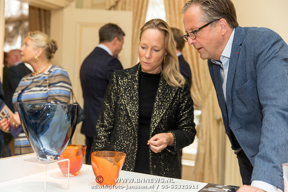 NLD/Den Haag/20190919 - Prinses Margarita exposeert op Masterly The Hague, Prinses Margarita geeft uitleg over haar ontworpen oranje vaasje '75 jaar vrijheid'  aan Alexander Pechteld