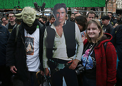© Licensed to London News Pictures. 16/12/2015. London, UK. A fan stands with a full sized photo of Han Solo as an other wears a Yoda mask in Leicester Square ahead of the UK premiere of Star Wars: The Force Awakens. Photo credit: Peter Macdiarmid/LNP