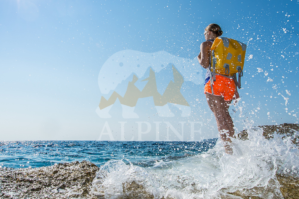 A female photographer wearing a yellow waterproof backpack as seen on a sunny Summer day standing on the coast line of Croatian natural park of Premantura.