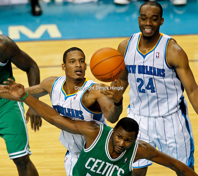 December 28, 2011; New Orleans, LA, USA; New Orleans Hornets small forward Trevor Ariza (1) reaches for the ball over Boston Celtics guard Keyon Dooling (51) during the fourth quarter of a game at the New Orleans Arena. The Hornets defeated the Celtics 97-78.  Mandatory Credit: Derick E. Hingle-US PRESSWIRE