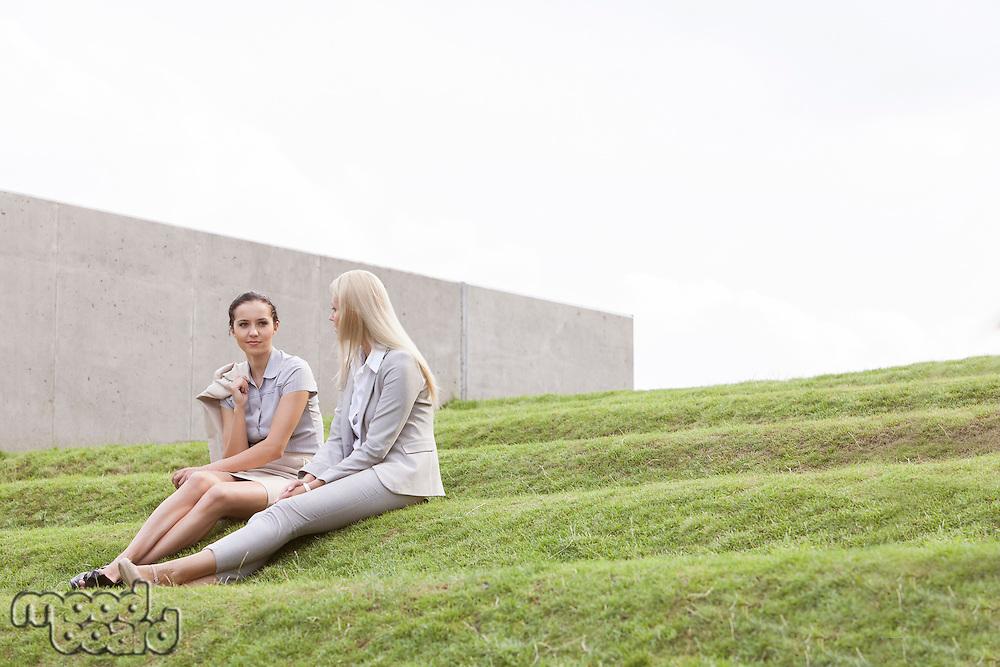 Full length of businesswomen sitting on grass steps against sky