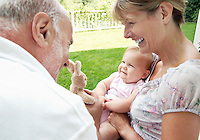 Grandparents playing with granddaughter in garden