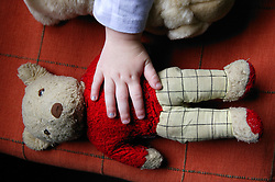 Close up of young child's hand touching a teddy bear,
