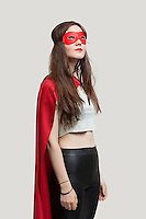 Young woman in superhero costume looking up against gray background