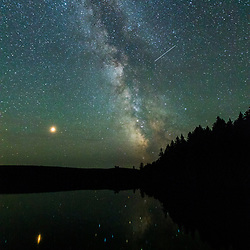 A shooting star and the Milky Way above Island Pond at Red River Camps in Aroostook County, Maine. Deboullie Public Reserve Land.