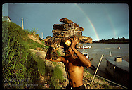 Man carries block of crude rubber from boat up steep river bank to be processed in Eirunepe, AM Brazil