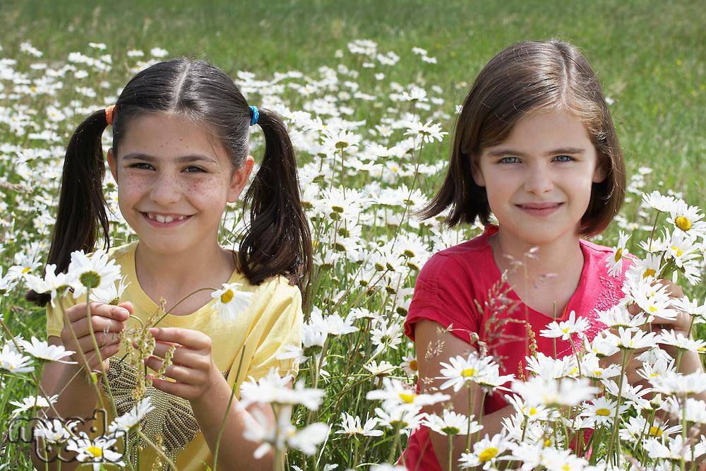 Two girls(7-9) standing among flowers in meadow portrait
