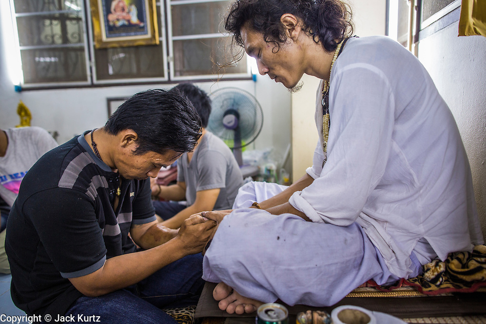 """23 MARCH 2013 - NAKHON CHAI SI, NAKHON PATHOM, THAILAND: A man (left) is blessed after getting a sacred Sak Yant tattoo at Wat Bang Phra. Wat Bang Phra is the best known """"Sak Yant"""" tattoo temple in Thailand. It's located in Nakhon Pathom province, about 40 miles from Bangkok. The tattoos are given with hollow stainless steel needles and are thought to possess magical powers of protection. The tattoos, which are given by Buddhist monks, are popular with soldiers, policeman and gangsters, people who generally live in harm's way. The tattoo must be activated to remain powerful and the annual Wai Khru Ceremony (tattoo festival) at the temple draws thousands of devotees who come to the temple to activate or renew the tattoos. People go into trance like states and then assume the personality of their tattoo, so people with tiger tattoos assume the personality of a tiger, people with monkey tattoos take on the personality of a monkey and so on. In recent years the tattoo festival has become popular with tourists who make the trip to Nakorn Pathom province to see a side of """"exotic"""" Thailand. The 2013 tattoo festival was on March 23.    PHOTO BY JACK KURTZ"""